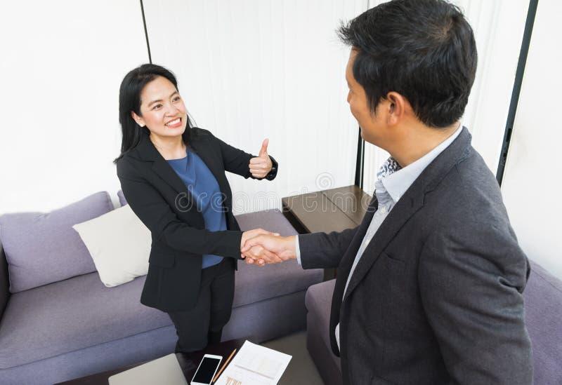 Mulher de negócio do sorriso e homem de negócio que agita a mão e o polegar acima foto de stock