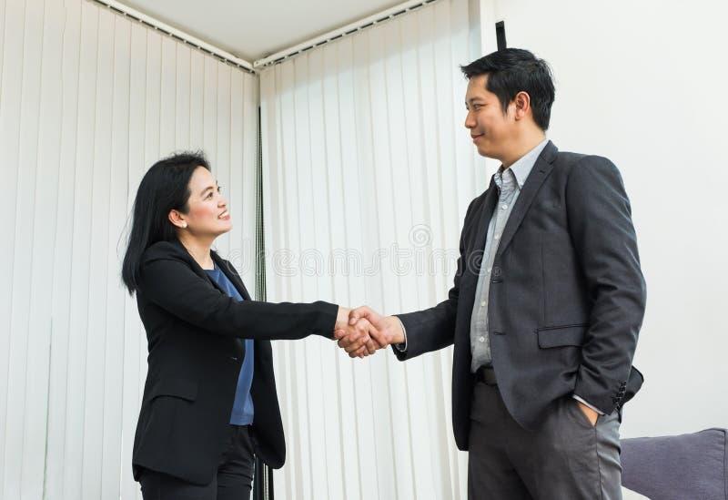 Mulher de negócio do sorriso e homem de negócio que agita a mão no escritório, Pa fotos de stock royalty free