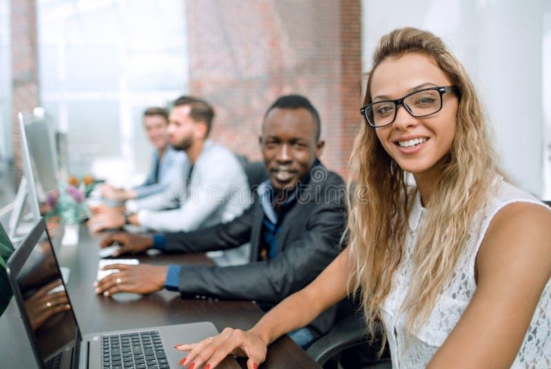 Mulher de negócio e um grupo de empregados na sala de computador imagem de stock