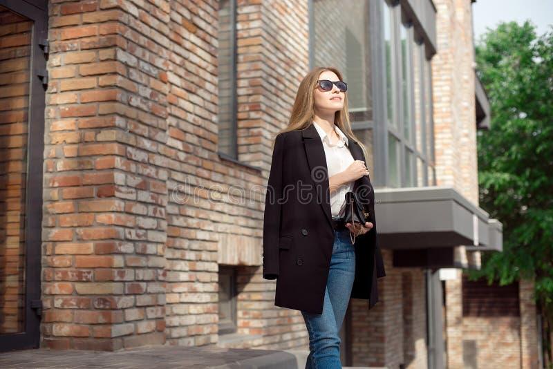 Mulher de negócio elegante nova Modelo fêmea à moda em uma blusa branca e na calças de ganga sunglasses O revestimento preto é fotos de stock royalty free