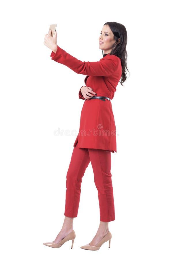 Mulher de negócio elegante segura bem sucedida que toma o selfie com telefone esperto Vista lateral imagens de stock royalty free