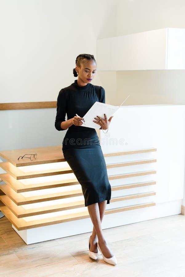 Mulher de negócio elegante severo que veste o vestido preto e sapatas bege no escritório claro que olha sua agenda, retrato compl imagens de stock