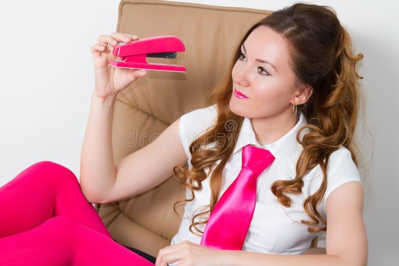 Mulher de negócio em calças justas cor-de-rosa e no laço cor-de-rosa imagem de stock