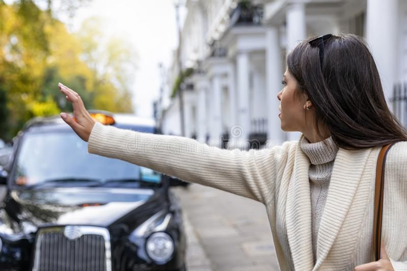 Mulher de negócio em Londres que sauda para um táxi preto imagem de stock royalty free