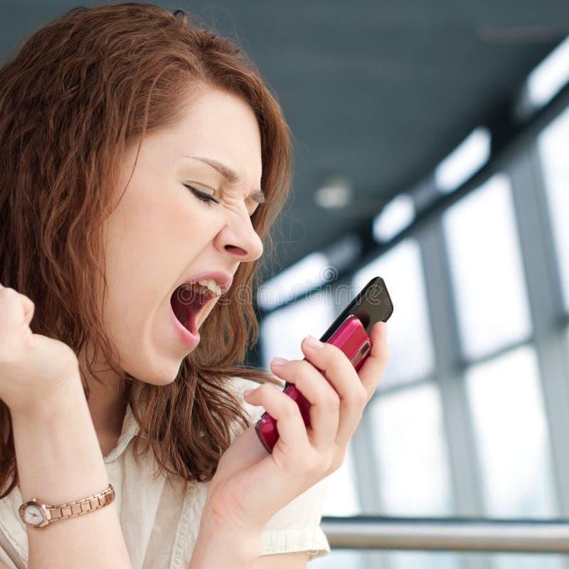 Mulher de negócio emocional com o telefone no café fotos de stock royalty free