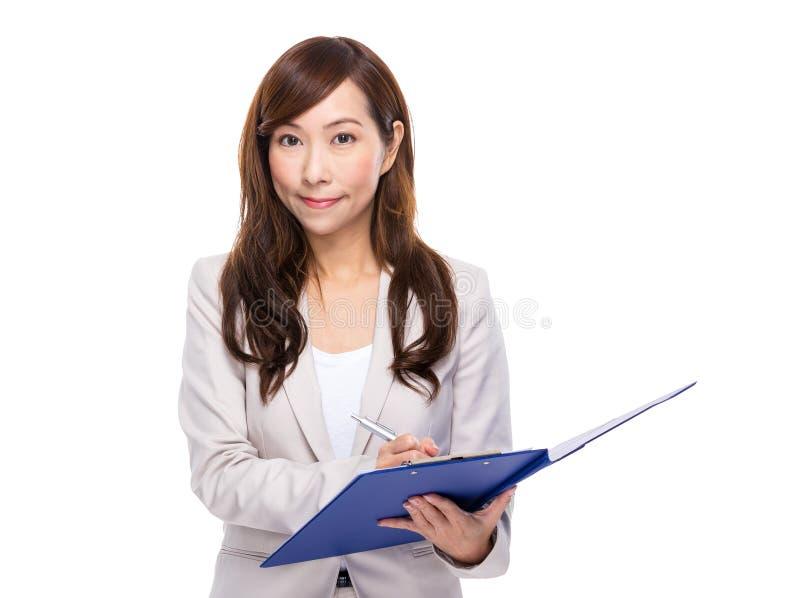 A mulher de negócio escreve algo na almofada do arquivo foto de stock royalty free