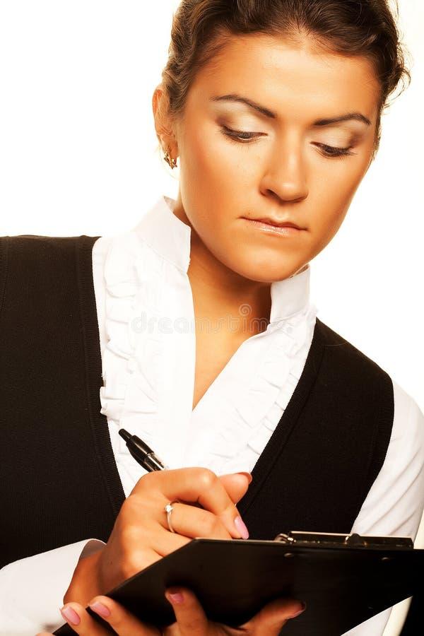 A mulher de negócio escreve na prancheta foto de stock