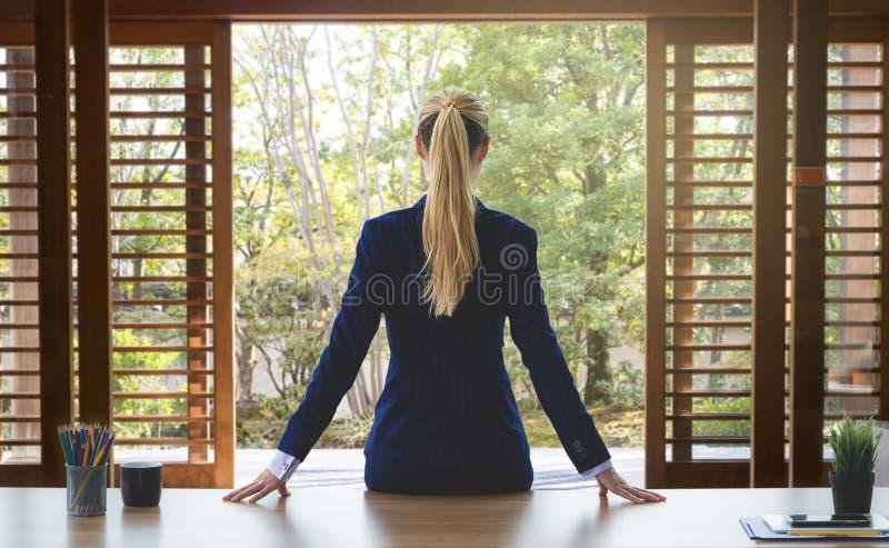 A mulher de negócio está olhando para fora as janelas do jardim para o succ imagens de stock royalty free