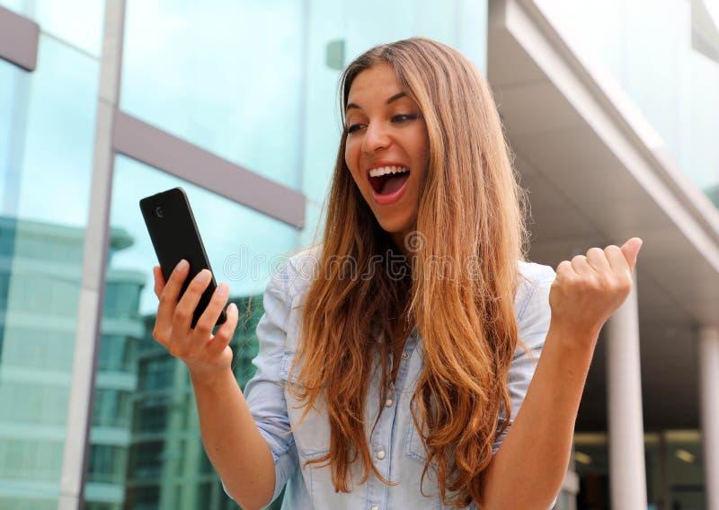 Mulher de negócio eufórico que olha seu telefone esperto e que mostra o gesto do vencedor exterior imagem de stock royalty free