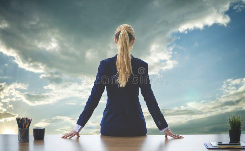 Mulher de negócio fêmea que olha para fora as janelas para o sucesso fotografia de stock royalty free