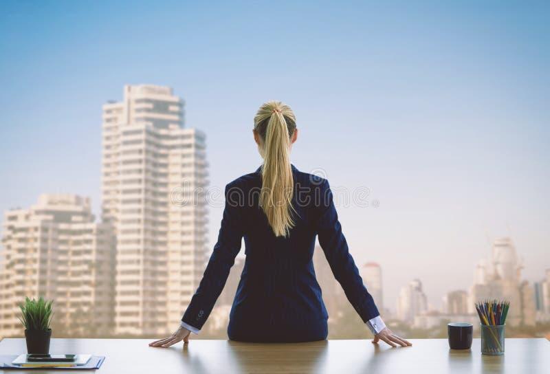 Mulher de negócio fêmea que olha para fora as janelas para o sucesso fotos de stock