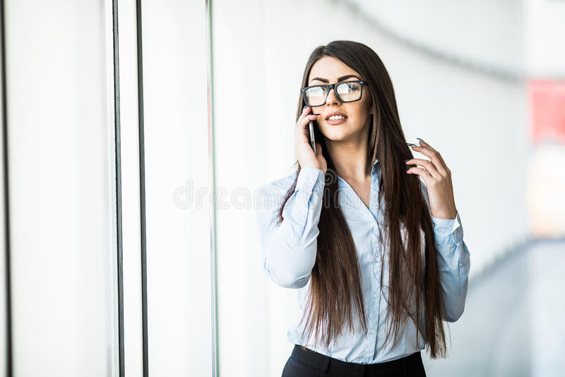 A mulher de negócio fala o telefone no salão do escritório fotografia de stock