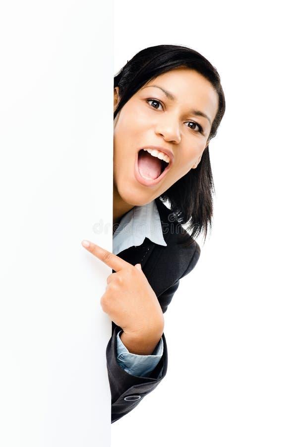 Mulher de negócio feliz da raça misturada que aponta no iso vazio do espaço da cópia imagem de stock royalty free