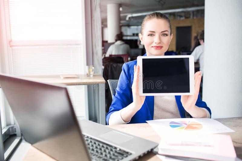 A mulher de negócio feliz está guardando uma tabuleta É desligado Está mostrando-o à câmera e ao sorriso fotos de stock royalty free