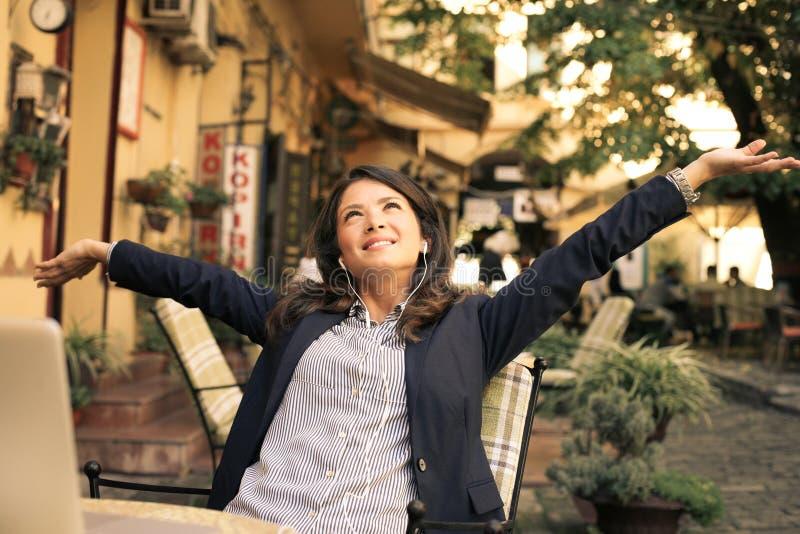 Mulher de negócio feliz na música de escuta do café, braços acima imagem de stock