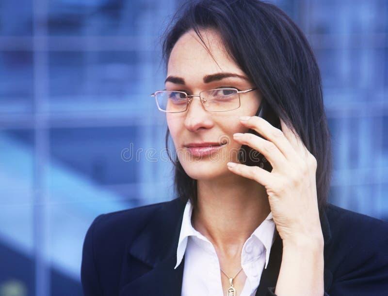 Mulher de negócio feliz nova bonita que sorri durante um telefonema imagens de stock royalty free