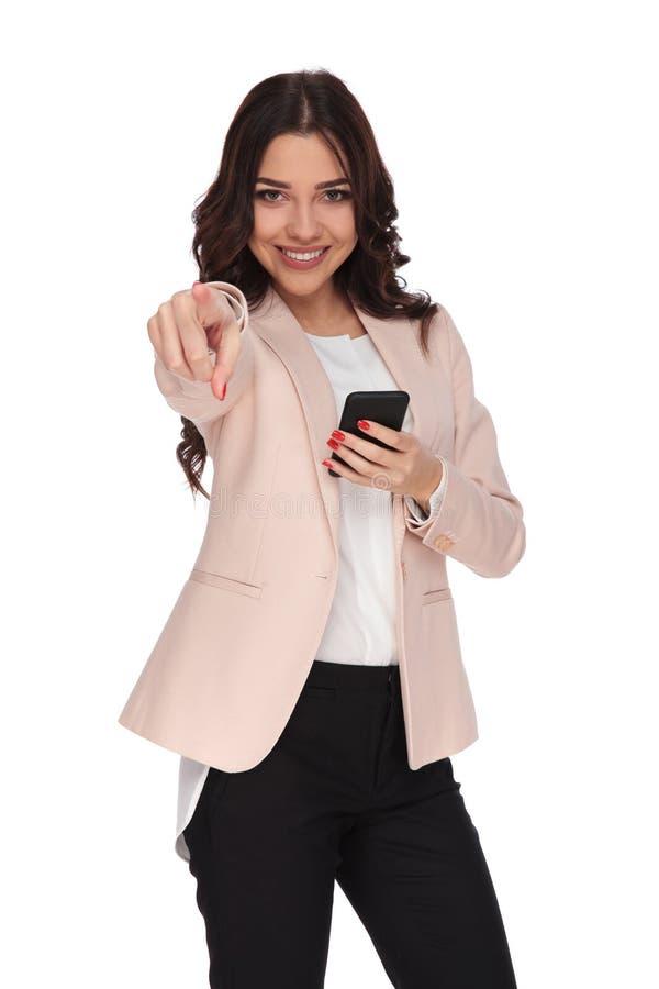 Mulher de negócio feliz nova que aponta o dedo ao texting no phon imagens de stock royalty free