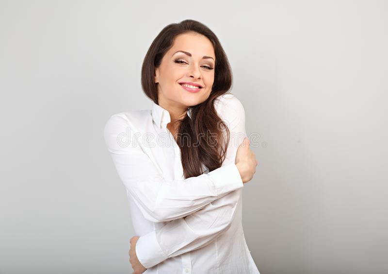 Mulher de negócio feliz que abraça-se com a cara de apreciação emocional natural com os olhos fechados no fundo azul Conceito do  imagem de stock