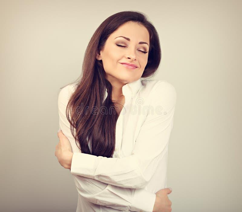 Mulher de negócio feliz que abraça-se com a cara de apreciação emocional natural com os olhos fechados no fundo da cor Conceito d imagens de stock