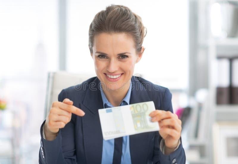 Mulher de negócio feliz que aponta no bloco do dinheiro fotografia de stock royalty free