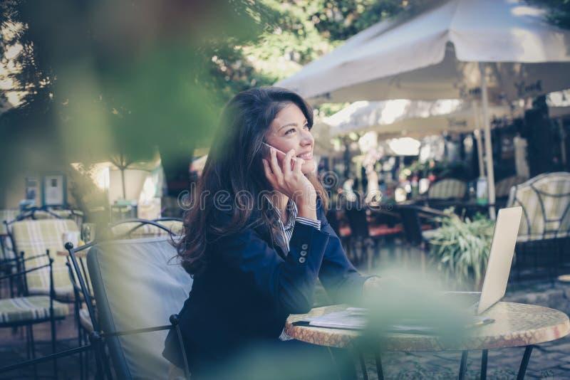 Mulher de negócio feliz que fala no telefone esperto outdoor imagem de stock royalty free