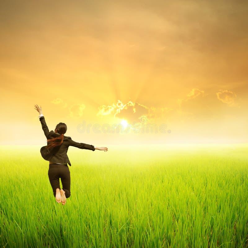 Mulher de negócio feliz que salta no campo verde do arroz