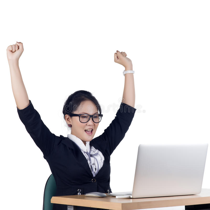 Mulher de negócio feliz que trabalha em um portátil no escritório