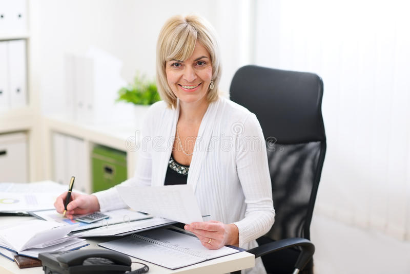Mulher de negócio feliz que trabalha no escritório imagem de stock