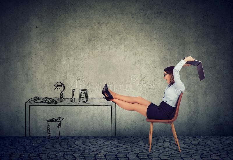 Mulher de negócio frustrante que senta-se em sua mesa louca com seu portátil incerto fotos de stock