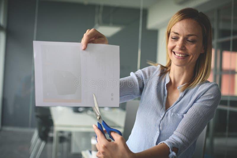 A mulher de negócio guarda tesouras e papel do corte Negócio feliz fotos de stock