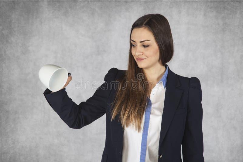 A mulher de negócio inclina o copo de café vazio imagem de stock royalty free