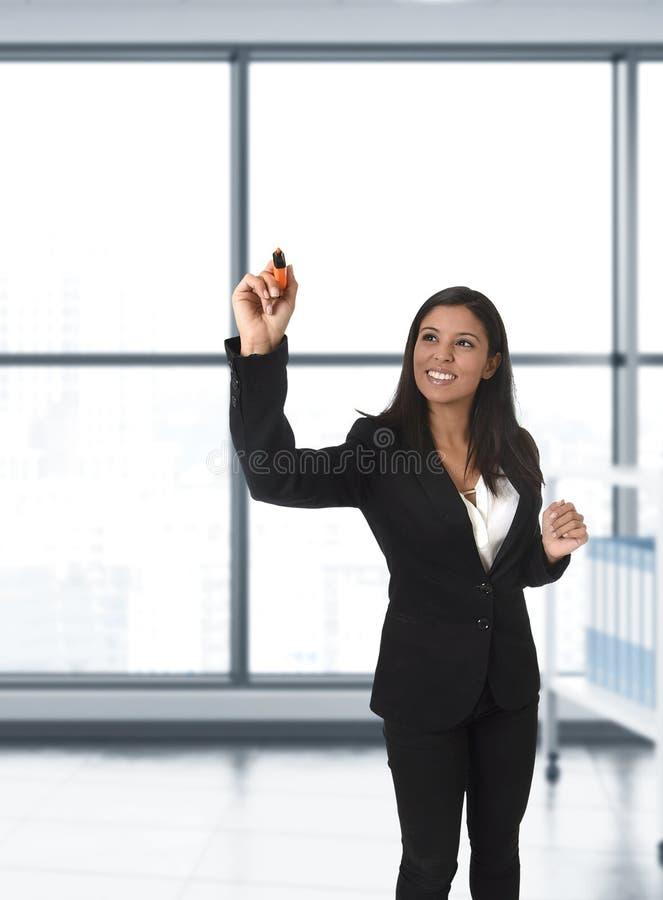 Mulher de negócio latino na escrita formal do terno com o marcador na tela virtual invisível ou placa no escritório moderno imagem de stock