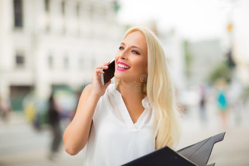 Mulher de negócio loura bonita no telefone exterior fotografia de stock