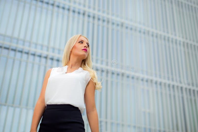 Mulher de negócio loura nova sobre o fundo moderno imagens de stock