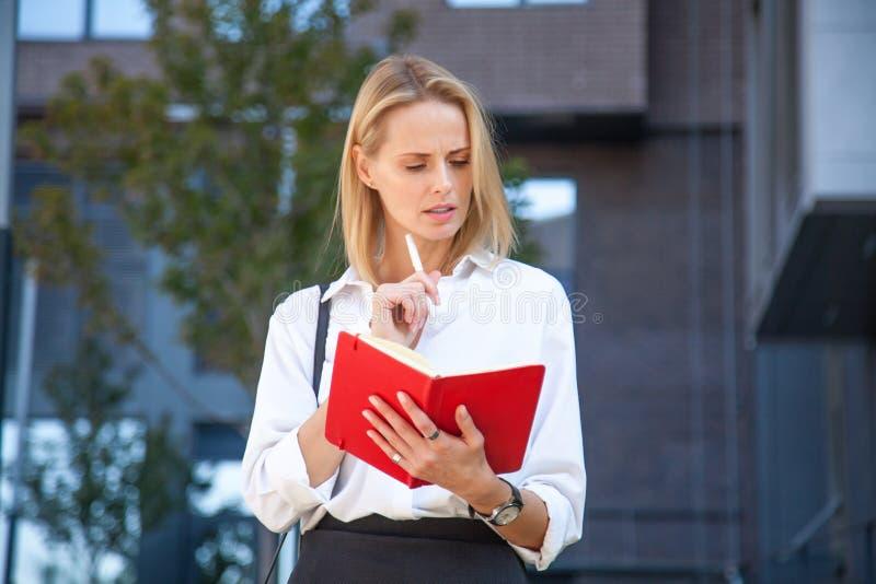 Mulher de negócio loura pensativa com o caderno contra do prédio de escritórios fotografia de stock royalty free