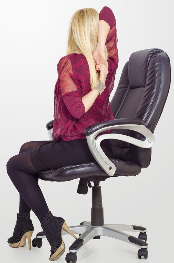 Mulher de negócio loura que estica ombros em seu escritório imagens de stock royalty free