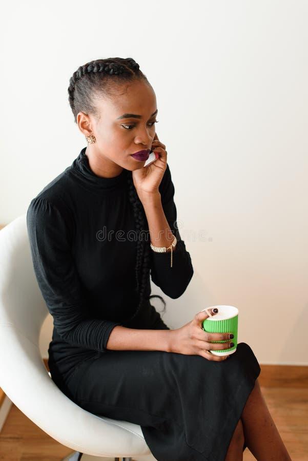 Mulher de negócio móvel no escritório que fala em seu telefone celular ao guardar o copo descartável fotografia de stock