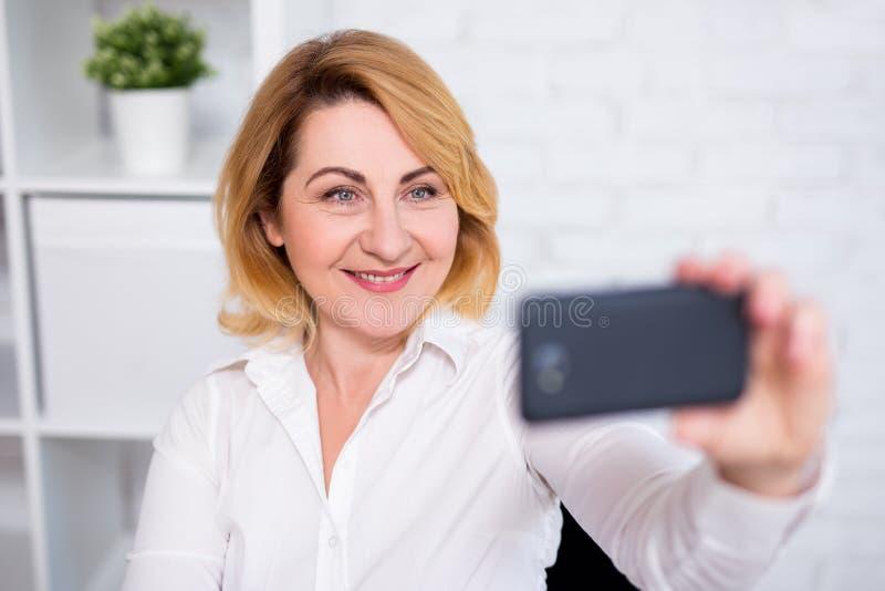 Mulher de negócio maduro alegre que toma a foto do selfie com telefone esperto foto de stock royalty free
