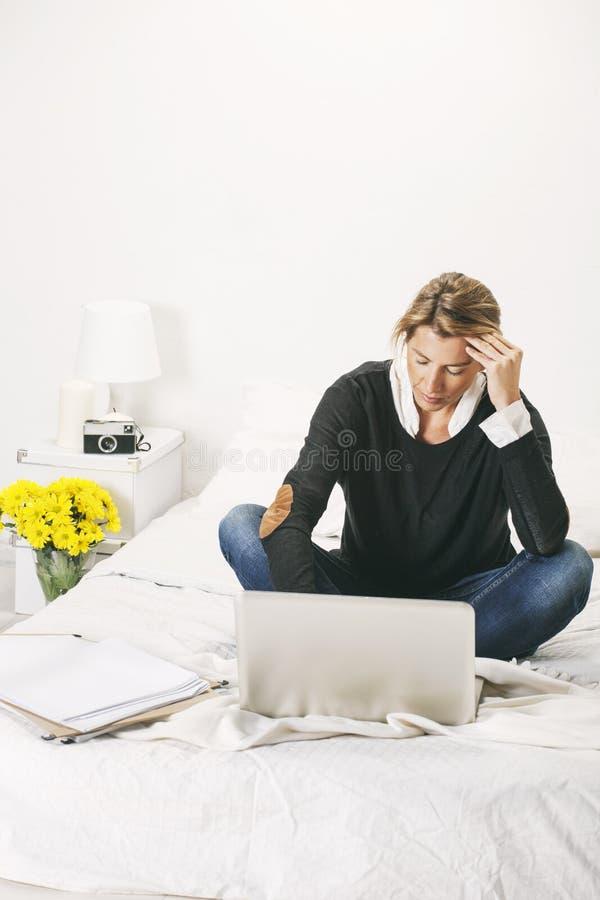 Mulher de negócio maduro bonita que trabalha com o portátil na cama. foto de stock royalty free