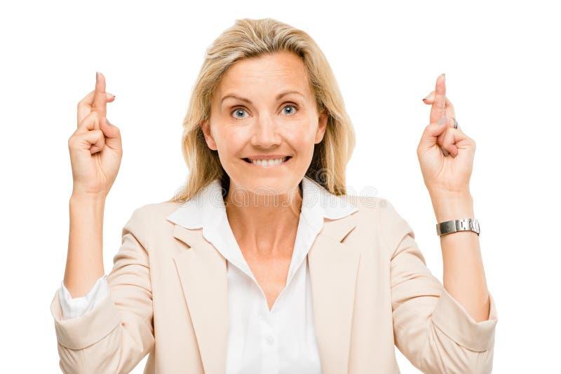 A mulher de negócio maduro que guarda os dedos cruzou-se isolado no branco foto de stock
