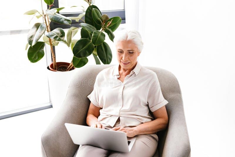 Mulher de negócio maduro de sorriso que trabalha no portátil imagens de stock