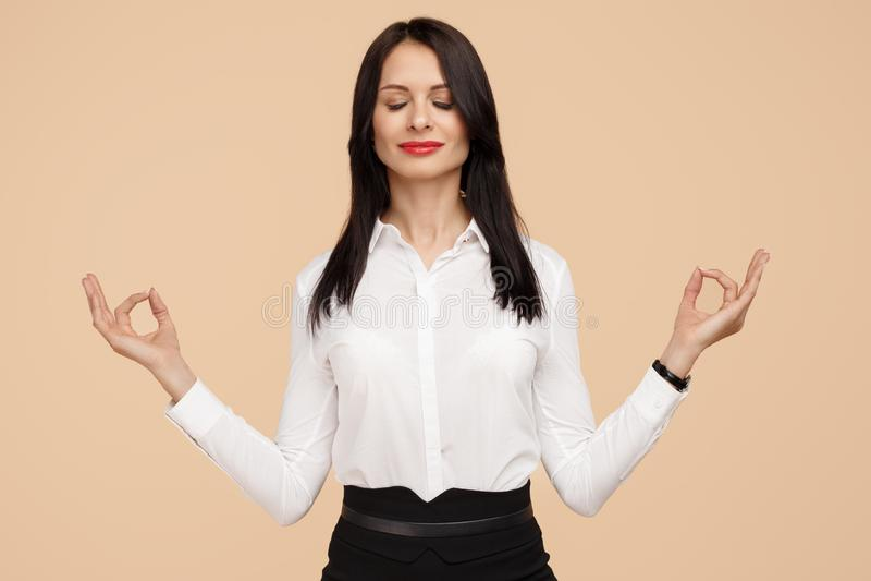 Mulher de negócio moderna nova feliz que medita sobre o fundo bege Meditação, religião e práticas espirituais imagens de stock