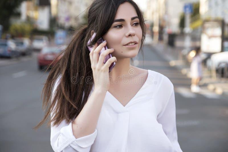Mulher de negócio moreno bonita na saia branca e na calças cinzenta do terno que fala em um telefone celular em suas mãos fora eu fotografia de stock royalty free