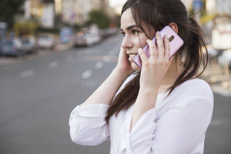 Mulher de negócio moreno bonita na saia branca e na calças cinzenta do terno que fala em um telefone celular em suas mãos fora eu fotos de stock