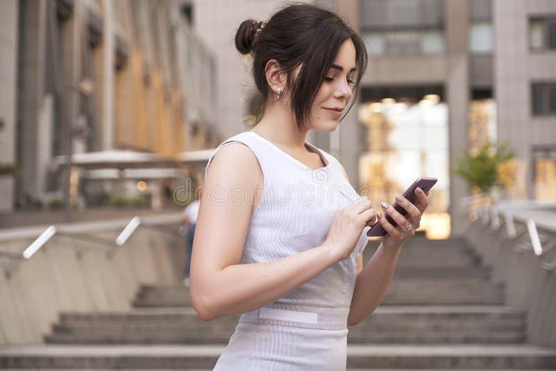 Mulher de negócio moreno bonita no vestido ocasional do smark cinzento que trabalha em um telefone celular em suas mãos fora Cida fotos de stock