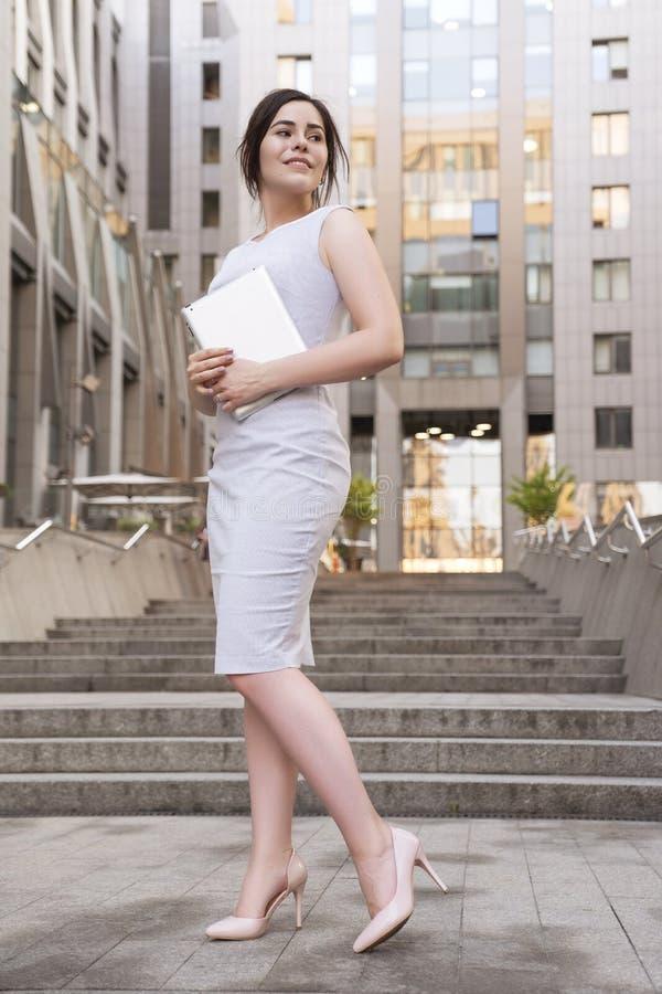 Mulher de negócio moreno bonita no vestido ocasional do smark cinzento que trabalha em uma tabuleta em suas mãos fora Cidade euro imagens de stock