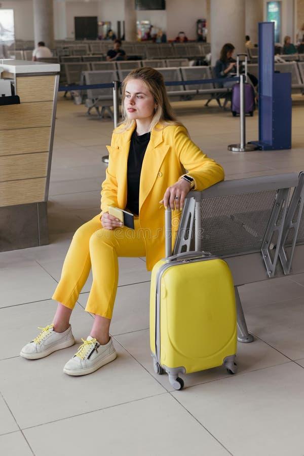 Mulher de negócio na área da partida do aeroporto que espera seu plano fotografia de stock royalty free