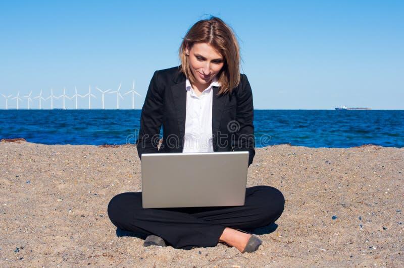 Mulher de negócio na areia com portátil imagens de stock royalty free