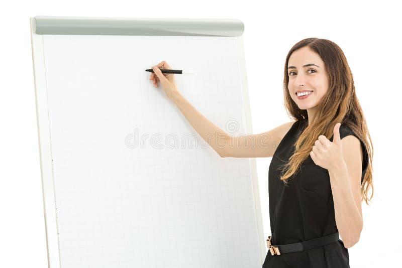 Mulher de negócio na frente de uma placa branca que dá os polegares acima fotos de stock royalty free