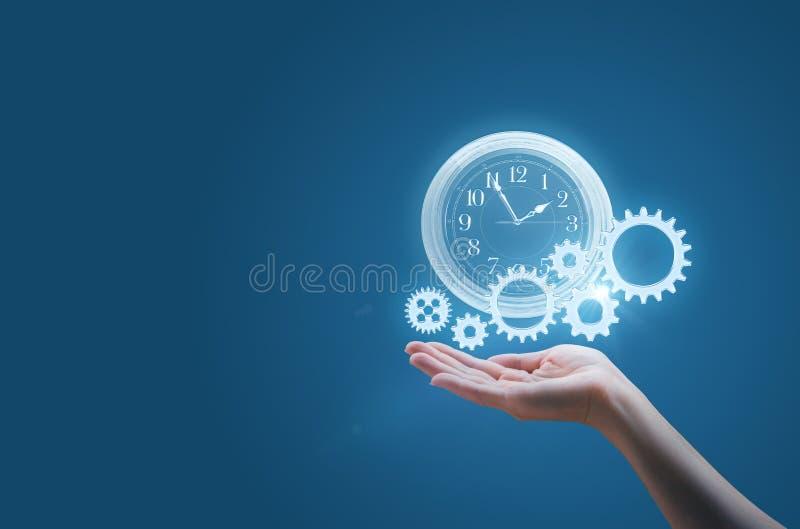 A mulher de negócio na palma de sua mão mantém o relógio e as engrenagens simbolizam o processo de um negócio bem sucedido fotografia de stock